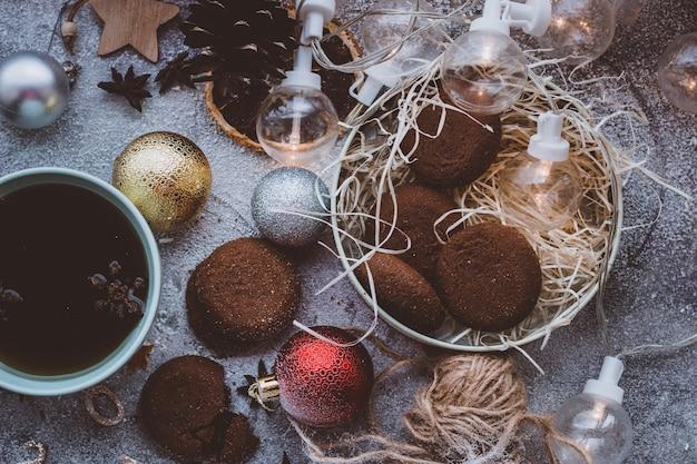 Biscotti e tè caldo caffè in una tazza sfondo scuro di capodanno atmosfera accogliente natalizia