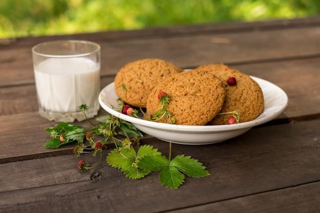 Biscotti e latte con fragola sul tavolo di legno con sfondo verde concetto di ricreazione