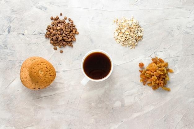 Biscotti, farina d'avena, caffè, uvetta e una tazza di caffè su uno sfondo chiaro. concetto di colazione