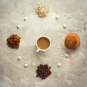 Biscotti, farina d'avena, caffè, uvetta e una tazza di tè al latte. concetto di una sana colazione