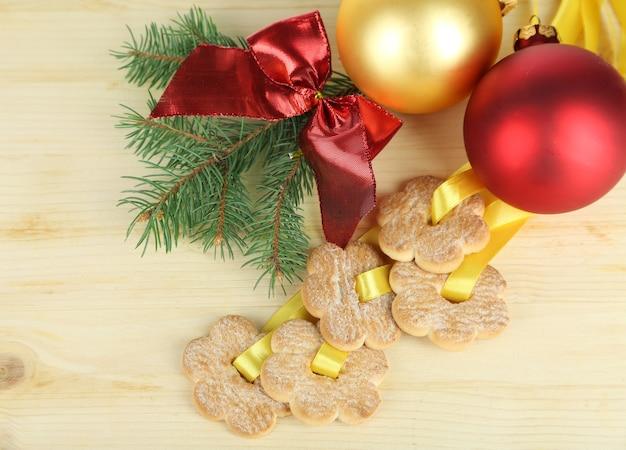 Biscotti su nastri con decorazioni natalizie su tavola di legno
