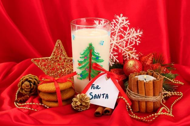 Biscotti per babbo natale: immagine concettuale di biscotti allo zenzero, latte e decorazioni natalizie su sfondo rosso