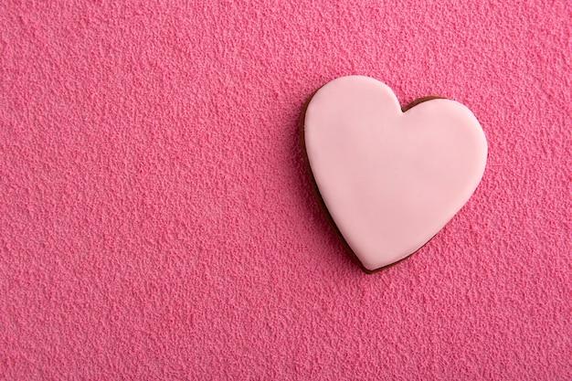 Biscotti a forma di cuori con glassa di zucchero su sfondo rosa.