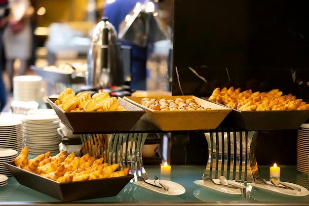 Biscotti o piccole torte in una ciotola a un tavolo da buffet.