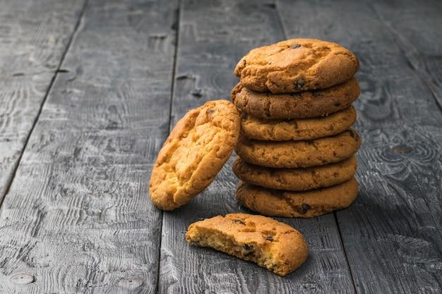 Biscotti con cereali e cioccolato su un tavolo di legno nero