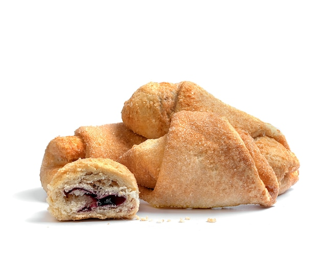 Biscotti con marmellata di amarene cosparsi di zucchero su fondo bianco