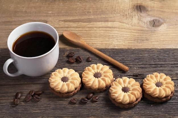 Biscotti con cioccolato e tazza di caffè nero per colazione sul vecchio tavolo di legno