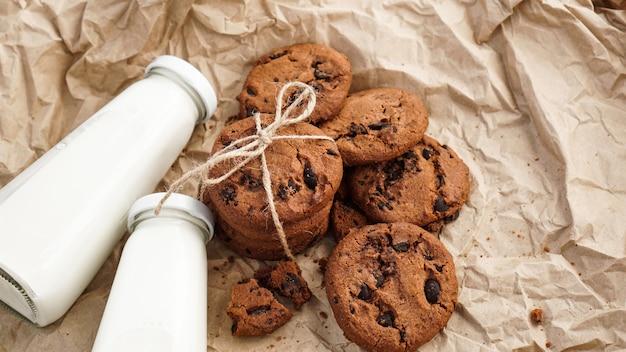 Biscotti con gocce di cioccolato su carta artigianale e bottiglie di latte. serpenti biologici naturali fatti a mano per una sana colazione