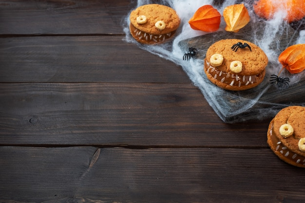 Biscotti con pasta di crema a forma di mostri per la festa di halloween. divertenti facce fatte in casa fatte di biscotti di farina d'avena e latte condensato bollito. copia spazio