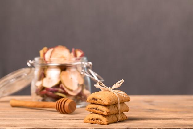 Biscotti con marmellata legati con una corda, un vasetto di frutta secca di mele e arance e un cucchiaio per il miele.