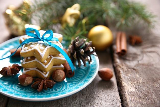 Biscotti con spezie e decorazioni natalizie, su tavola di legno