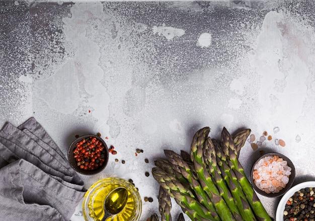 Cottura dello sfondo di asparagi. mazzo di asparagi organici verdi freschi pronti per la cottura su teglia con olio d'oliva e condimenti, buono per una dieta sana, vista dall'alto, primo piano, spazio per il testo