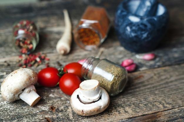 Fondo di cottura con condimento diverso. spezie e verdura, primo piano. stile rustico. cucina di cibi e spezie. sfondo di cibo. ingredienti su tavola di legno scuro.
