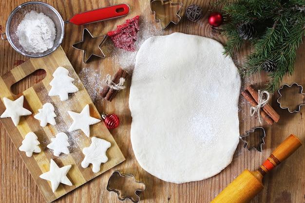 Cucinare biscotti al burro di forme diverse su un tavolo di legno con accessori natalizi