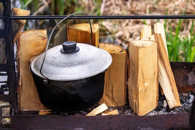 Cottura in un calderone di ghisa su un treppiede su un fuoco aperto. messa a fuoco selettiva