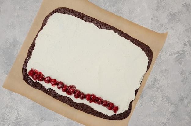 Cucinare la torta al cioccolato con ripieno di crema e ciliegie. rotola foresta nera su uno sfondo grigio cemento. ricetta passo dopo passo. vista dall'alto.