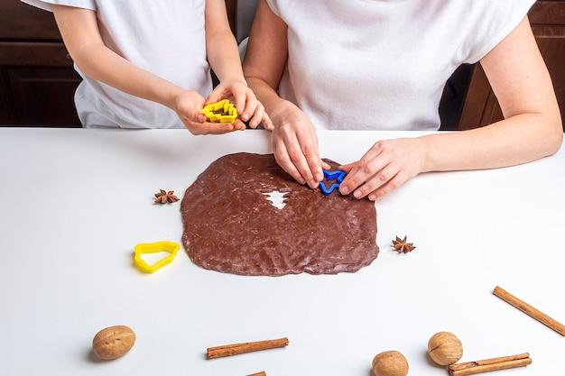 Cucinare biscotti al cioccolato di natale e capodanno o pan di zenzero. cottura festiva tradizionale, infornare con i bambini. passaggio 11 ritagliare la pasta arrotolata con gli stampini. ricetta passo dopo passo