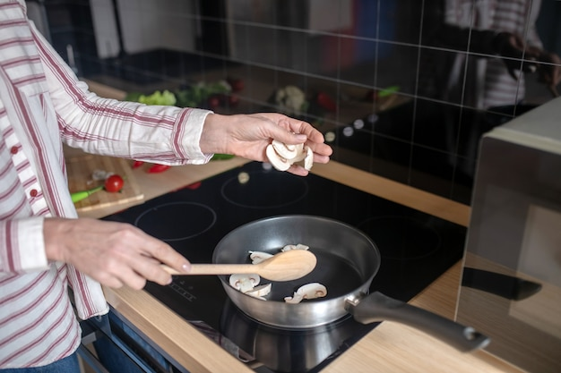 Cucinando. chiudere l immagine di una donna che mescola il cibo su una padella