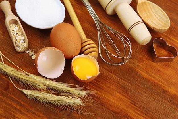 Concetto di cucina. ingredienti di cottura di base e utensili da cucina sulla tavola di legno