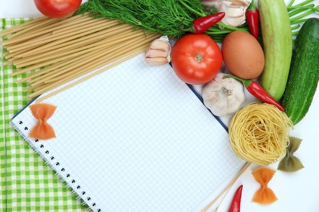 Concetto di cucina. primo piano di generi alimentari con libro di cucina vuoto