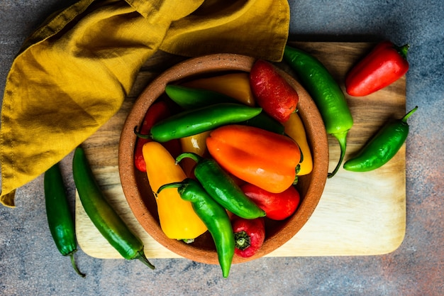Concetto di cucina con peperoni crudi grezzi su sfondo di pietra