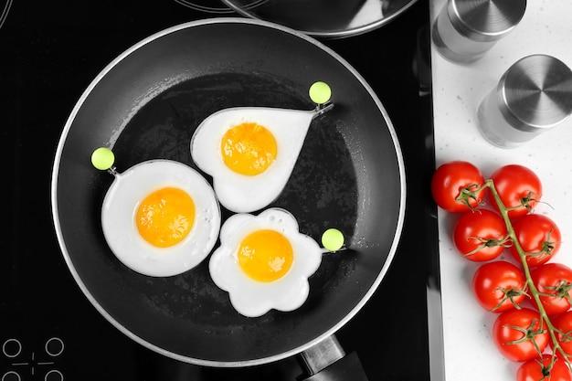 Cottura di deliziose uova soleggiate in stampi, vista dall'alto