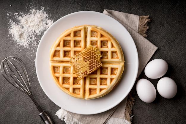 Cucinare deliziosi waffle con dolce nido d'ape, frusta in acciaio, uova - sfondo di pietra, stile scuro
