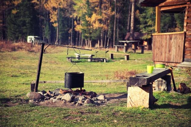 Cucinare la cena in una pentola sul fuoco. concetto di pausa pranzo in campeggio.