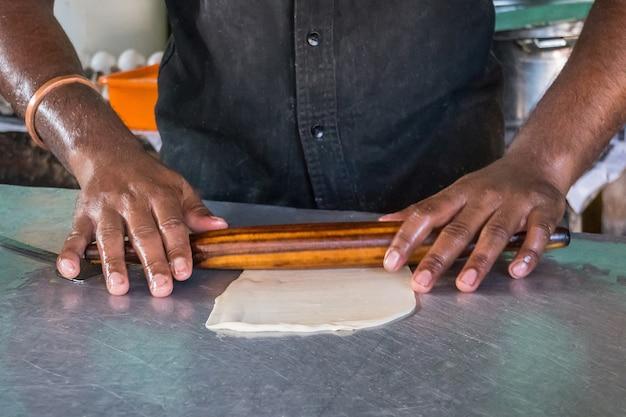 Cottura dell'impasto per la cottura in cucina, torte già pronte per la cottura, le mani dello chef preparano l'impasto per fare torte, rotoli di pasta con un mattarello. cibo di strada indiano. india. pizza. paratha