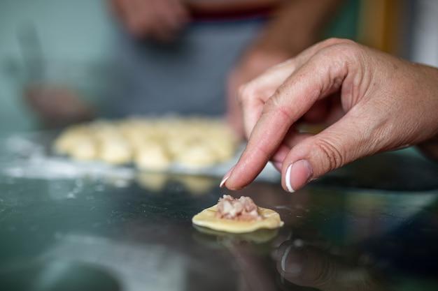 Cottura degli gnocchi da pasta e primo piano della carne macinata