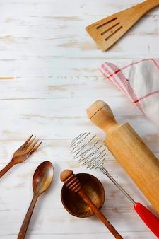 Utensili da cucina e da mangiare su un tavolo di legno bianco