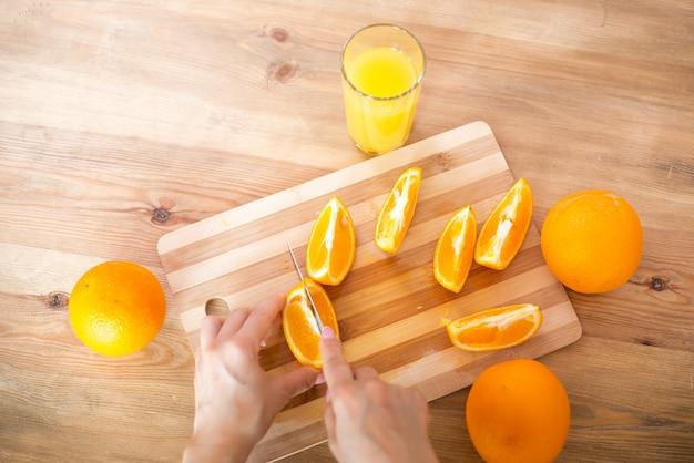 Cucinare il cibo e il concetto di vigore del veganismo e mangiare sano primo piano della mano femminile che taglia l'arancia a fette