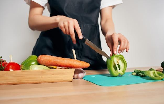 Cucinare cibo cibo sano cucina grembiule nero tagliare le verdure. foto di alta qualità