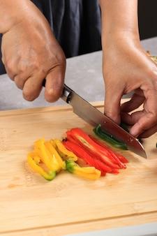 Cucina, cibo e concetto di cucina domestica, taglio a mano femminile peperone dolce a tre colori o paprica sul tagliere a casa, processo di cottura passo dopo passo