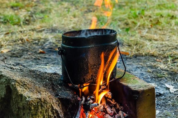 Cucinare il cibo in un bollitore sul falò nella foresta