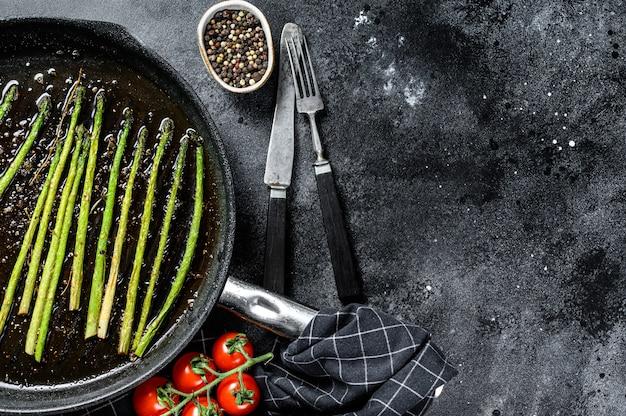 Cucinare gli asparagi freschi in una padella grigliata. vista dall'alto. copia spazio