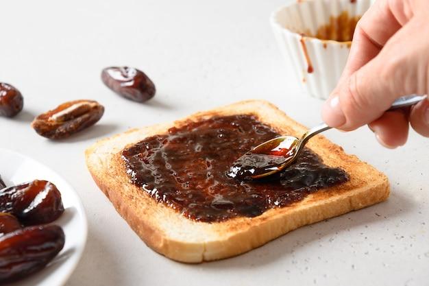 Cucinare pane tostato croccante fresco con marmellata di datteri sul tavolo bianco