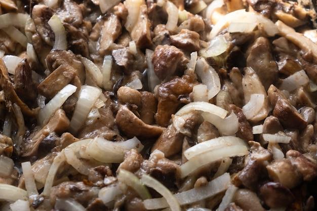 Cucinare i funghi fritti con le cipolle mescolare i funghi