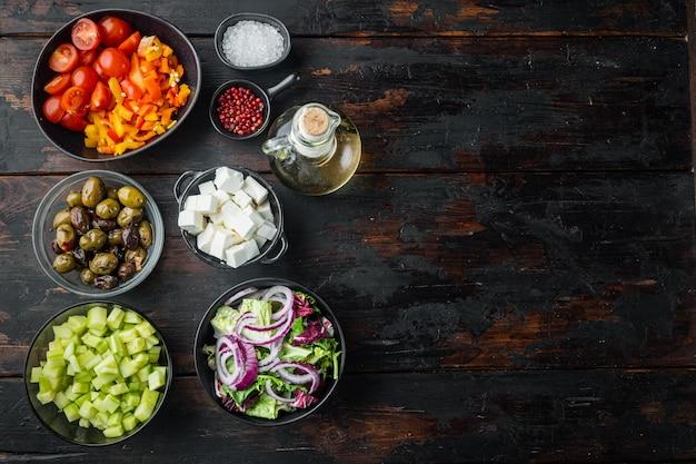 Cucinare l'ingrediente dell'insalata greca, su un vecchio sfondo di tavolo in legno scuro, vista dall'alto piatta con spazio di copia per il testo