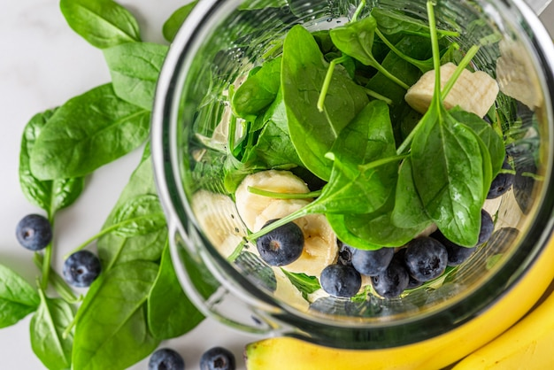 Cucinare un frullato sano o un frappè con mirtilli freschi, banana e spinaci nel frullatore