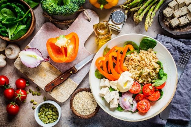 Cucinare cibi vegani sani. ingredienti per insalata di verdure con tofu e quinoa.