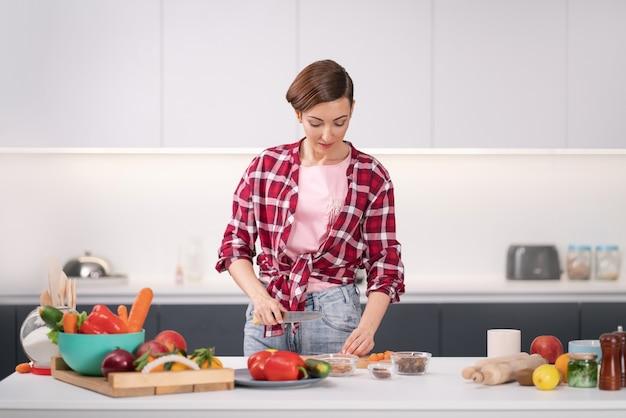 Cucinare a casa per amare la famiglia. preparare gli ingredienti sul tavolo giovane donna che cucina un pranzo in piedi in cucina.