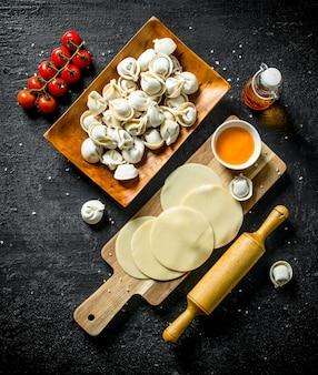 Cucinare gnocco crudo domestico sulla tavola rustica nera