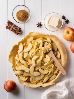 Cottura della torta di mele fatta in casa su un tavolo di legno