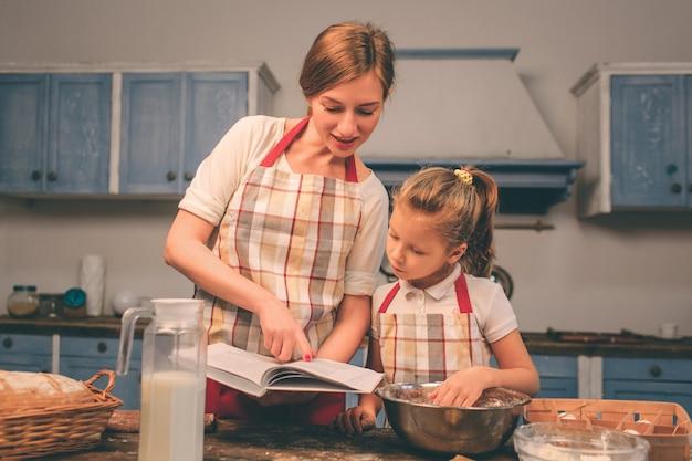 Cucinare torte fatte in casa. la famiglia amorosa felice sta preparando insieme il forno. la ragazza della figlia del bambino e della madre sta cucinando i biscotti e si sta divertendo nella cucina. alla ricerca di ricette in un libro culinario