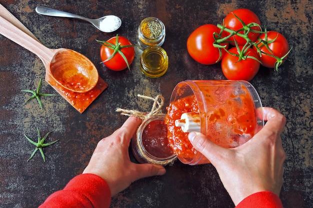 Cucinare la salsa di pomodoro fatta in casa. pomodori e spezie mani femminili in maniche lunghe rosse versano la salsa di pomodoro appena preparata da una tazza del frullatore in un barattolo di vetro.