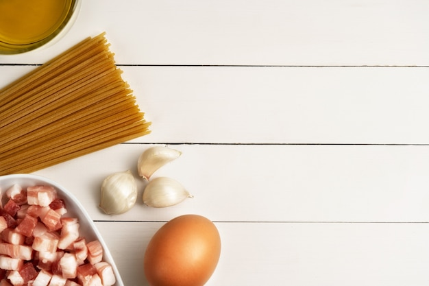 Ingredienti da cucina per la carbonara italiana su superficie rustica.