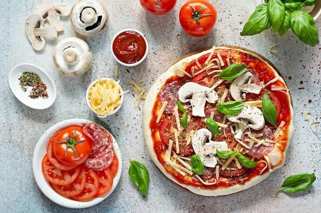 Cucinare la pizza italiana con salsa di pomodoro pomodori freschi formaggio funghi fette di salame e basilico