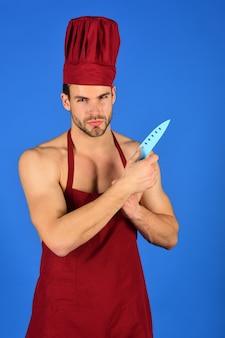 Cucinare stoviglie e persone concetto uomo cucinare in grembiule e cappello tiene chef coltello fiducioso maschio