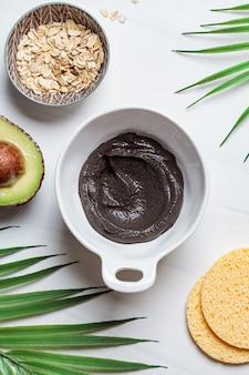 Maschera da cucina di argilla nera, avocado e farina d'avena, sfondo bianco. concetto di cura della pelle. pelle sana.